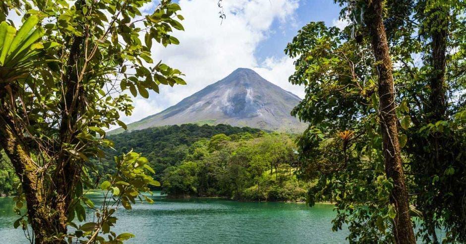 un volcán humeante visto a lo lejos desde un lago