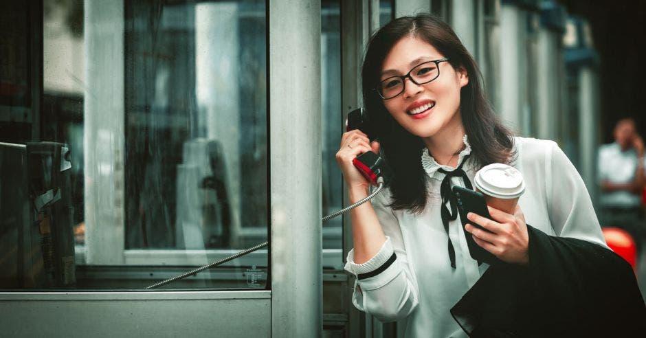 Mujer usando un teléfono público
