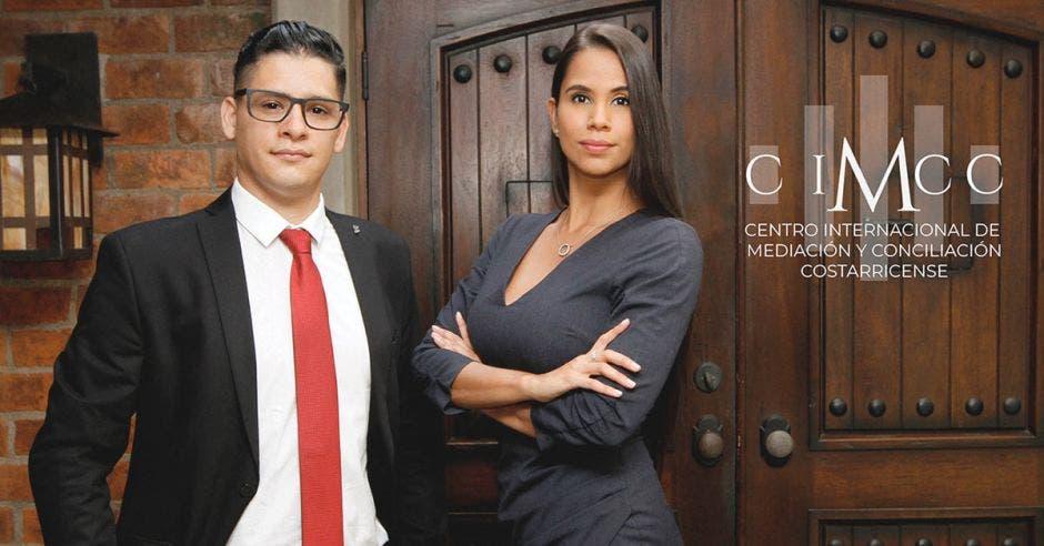 un hombre de anteojos y corbata roja junto a una mujer de vestido gris oscuro