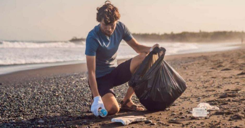 playa y persona recogiendo basura