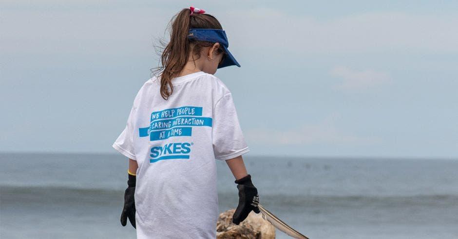 Un niña recoge basura en la playa