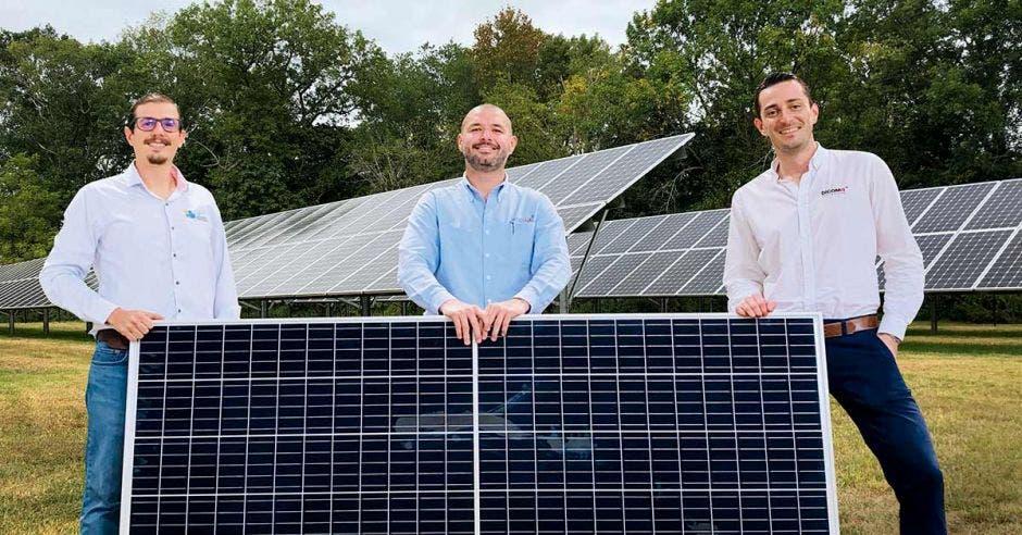 tres hombres posan junto a un panel solar