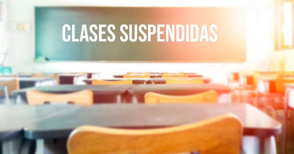 Un aula vacía y una pizarra que dice clases suspendidas