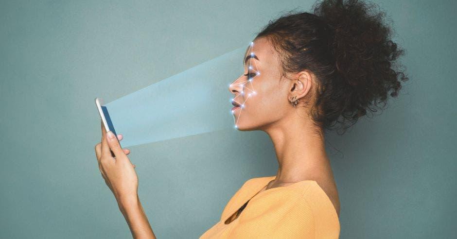 Identificación biométrica. Mujeres afroamericanas escaneando la cara con un sistema de reconocimiento facial en un smartphone
