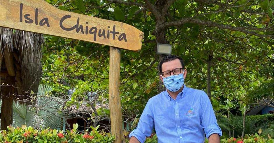 un hombre de camisa celeste y mascarilla posa junto a un letrero que dice Isla Chiquita