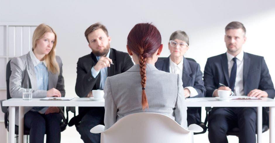 Mujer sentada siendo entrevistada por varias personas