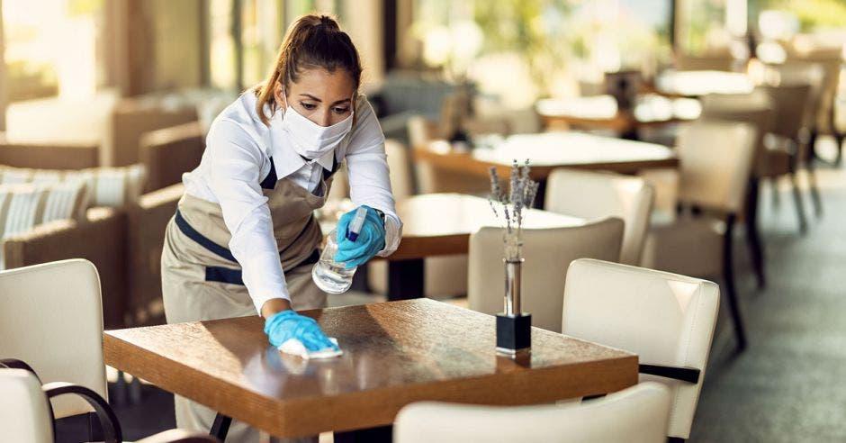 mesera con mascarilla limpiando una mesa