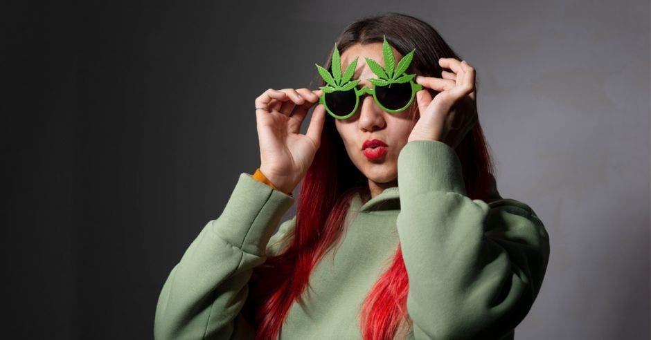 una mujer con anteojos en forma de hojas de marihuana