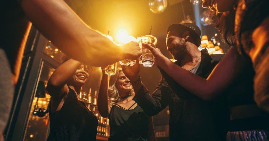 Imagen en ángulo bajo de un grupo de amigos disfrutando de bebidas en el bar juntos