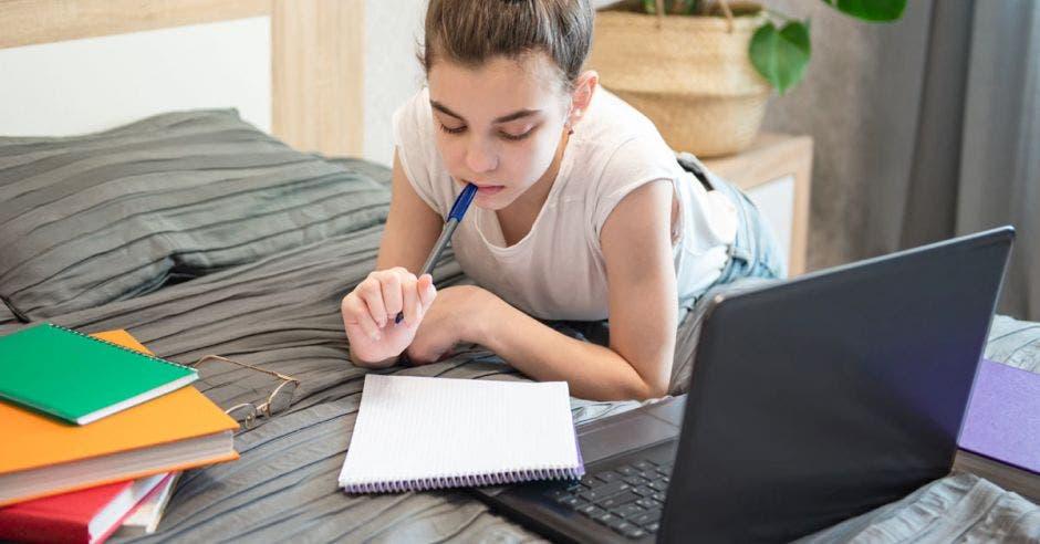 Una joven frente a una computadora y varios cuadernos en una cama