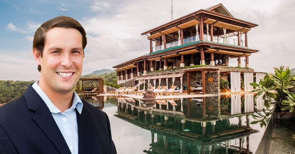 Un hombre de saco azul y camisa celeste con un hotel lujoso de fondo