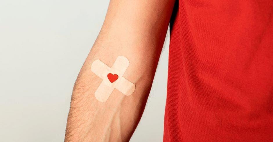 un joven de camisa roja con una marca del pinchazo de una inyección