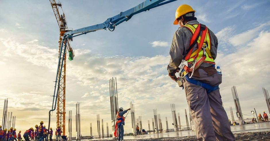 hombre con casco y uniforme parado en una construcción
