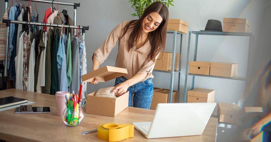 Joven empresaria guardando ropa en una caja