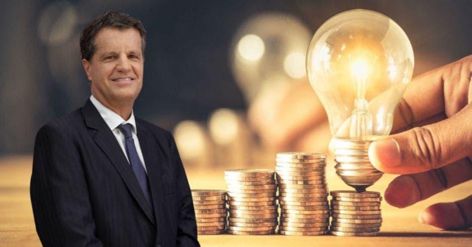 Hombre de traje frente a bombillo y monedas