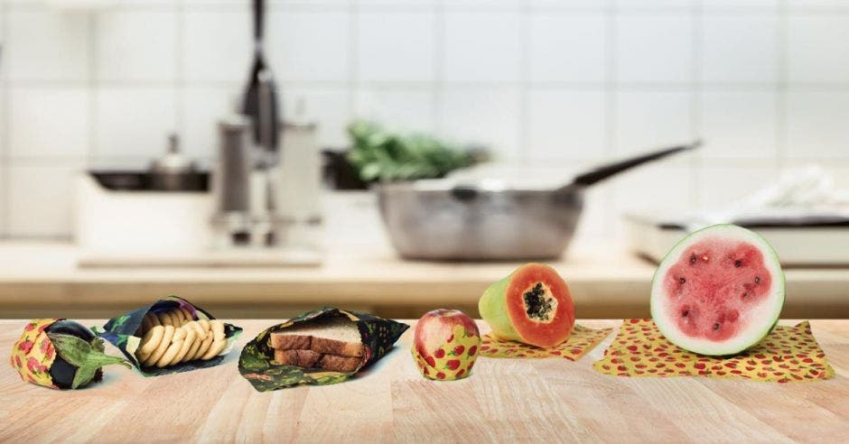 Un conjunto de alimentos dispuestos en una mesa: sandía, papaya, manzanas, biscochos , pan y lechuga