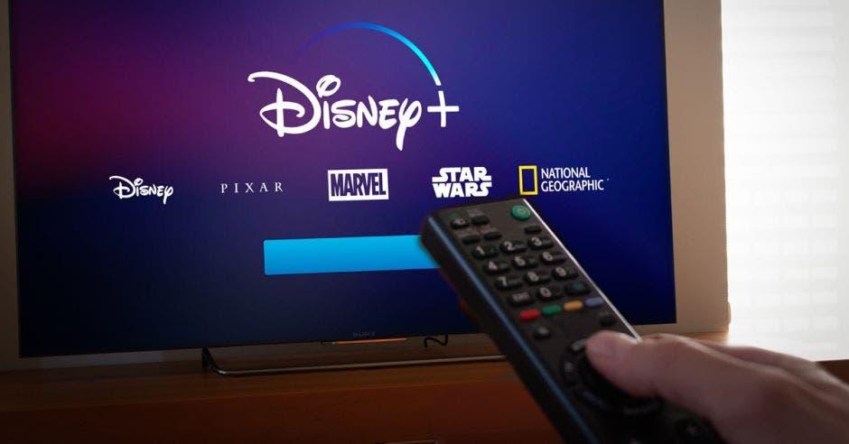 Disney+ en televisor y mano con control cambiando canal