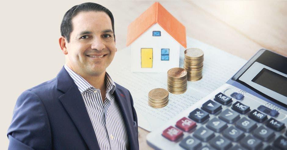Hombre sonriente frente a diseño pequeño de casa