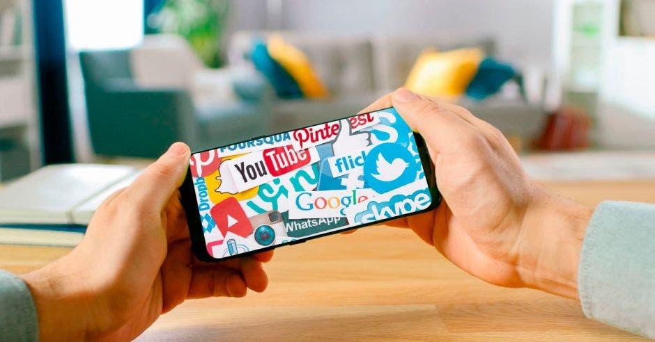 un hombre sostiene un celular con publicidad diversa en la pantalla