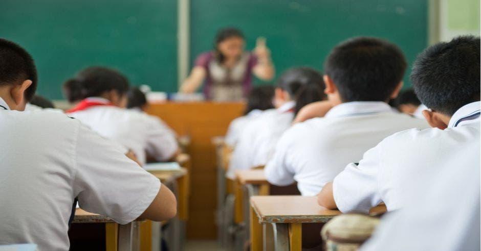 Un aula llena de alumnos y una educadora al fondo con una pizarra