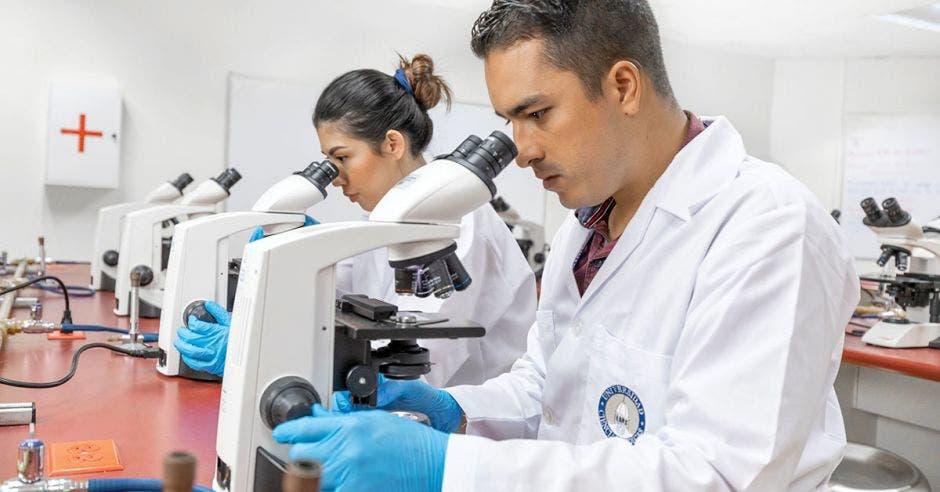 Dos estudiantes de UCIMED viendo un microscopio