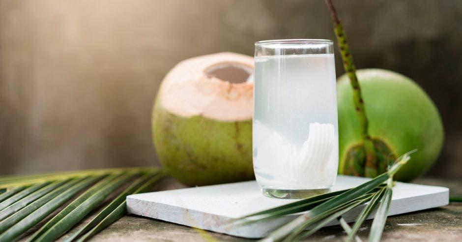 vaso con agua de coco y trozos de coco sobre una mesa blanca