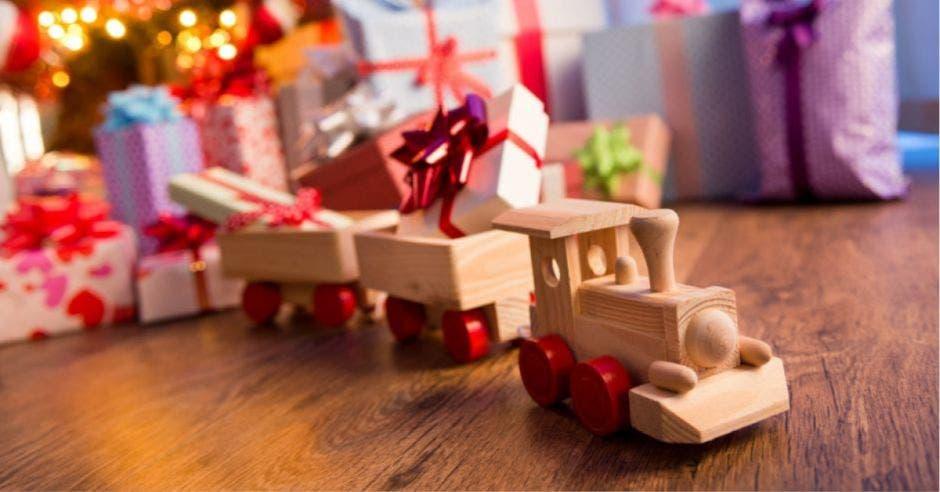 trenecito de madera con ruedas rojas y de fondo regalos de navidad