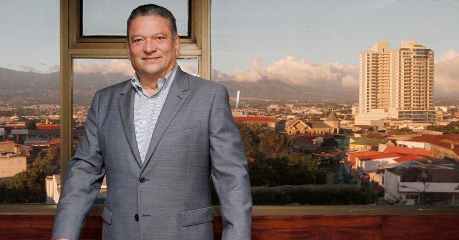 un hombre con saco gris frente a una ventana con una ciudad de fondo