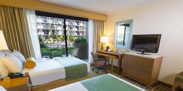 una habitación de hotel con dos camas, un escritorio y un televisor