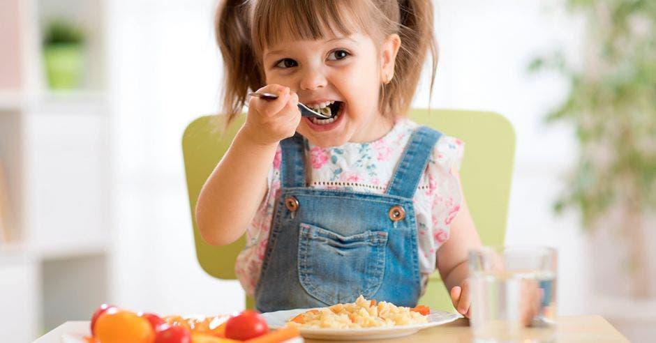 Una niña con una cuchara sentada comiendo