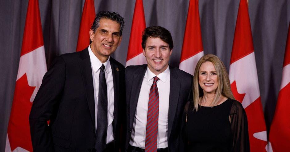 Personas de traje frente a bandera de Canadá