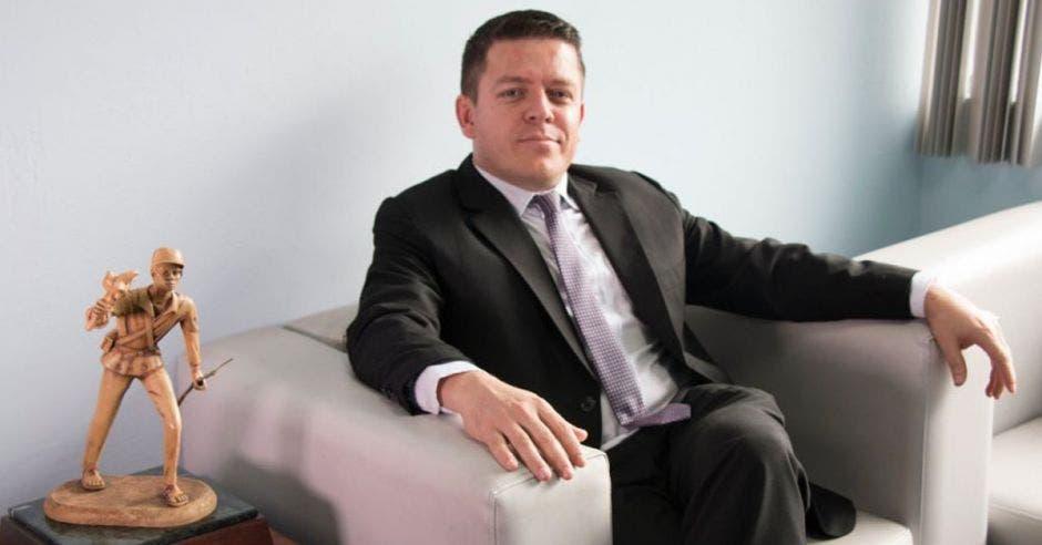 un hombre de saco y corbata sentado sobre un sillón blanco