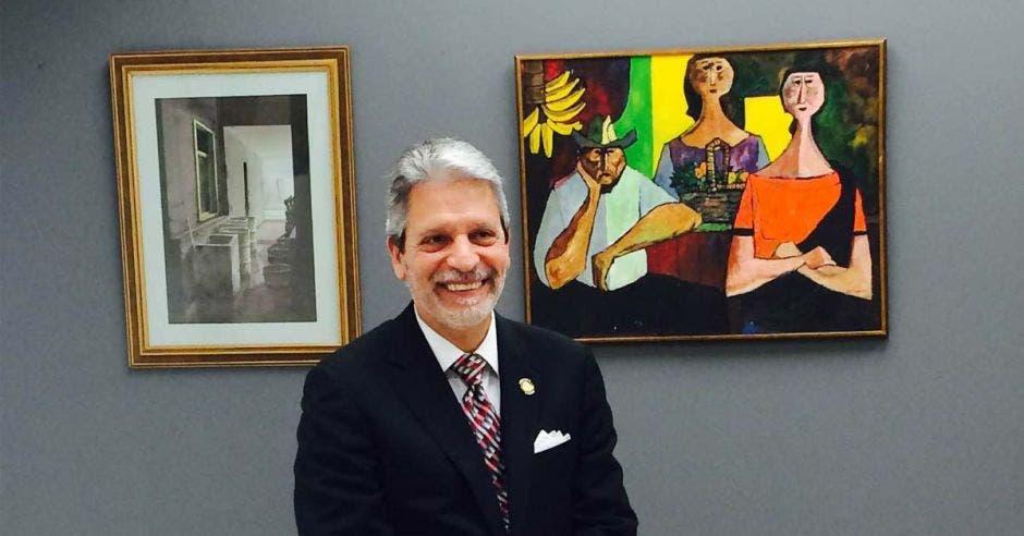 un hombre de pelo canoso en un cuarto con dos pinturas