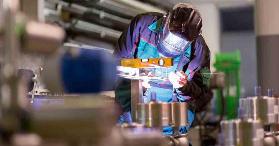 un hombre realiza trabajos de soldadura dentro de una fábrica
