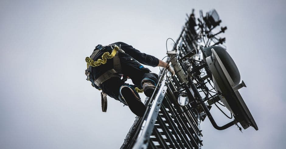 Trabajador subiendo una antena de telefonía móvil