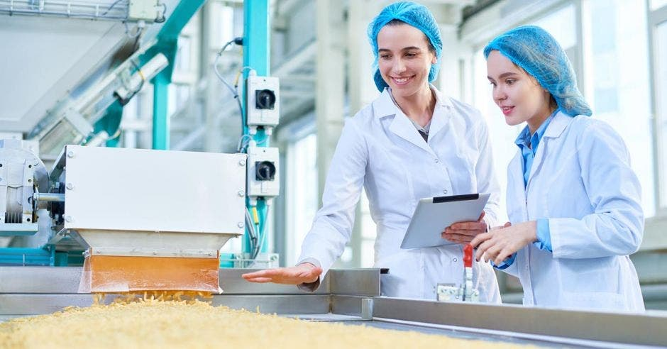 dos mujeres con bata y gorra trabajando en una fábrica de alimentos