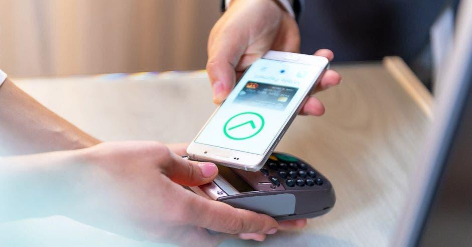 Persona con celular pagando en datáfono