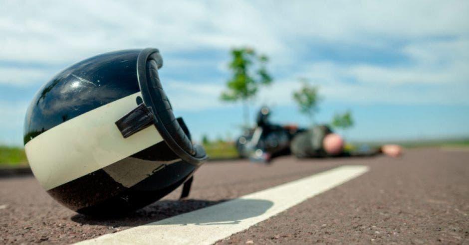 casco de motociclista tirado en la carretera