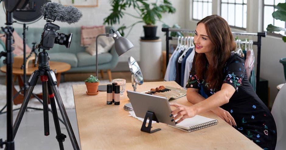 mujer sentada frente a una laptop y cámara de video