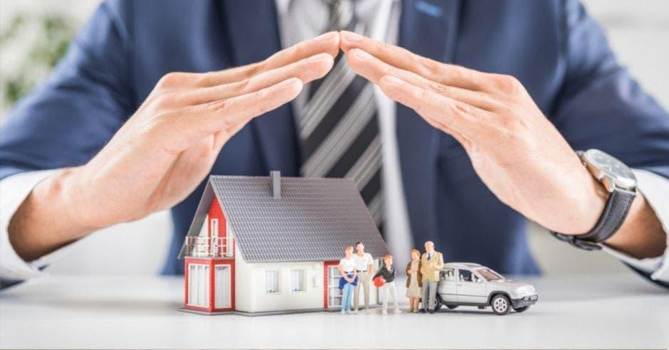 manos de hombre cubriendo una casa miniatura junto a figuritas de personas y un mini auto