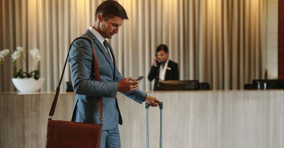 un hombre con una maleta de ruedas en el lobby de un hotel