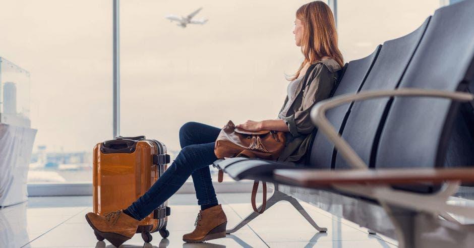 una mujer sentada en el lobby de un aeropuerto esperando su vuelo