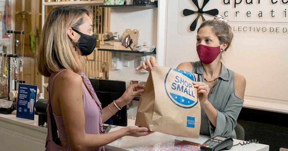 Mujeres pasándose bolsa de Shop Small