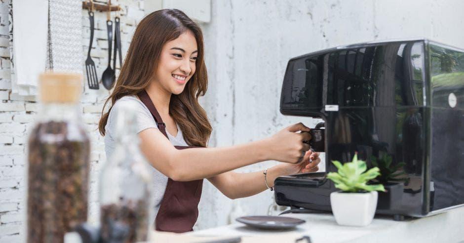 mujer con mandil marrón preparando un café
