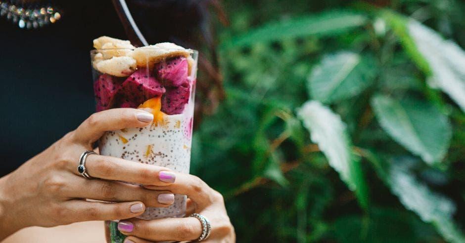 una mujer toma un batido de frutas en medio de la naturaleza