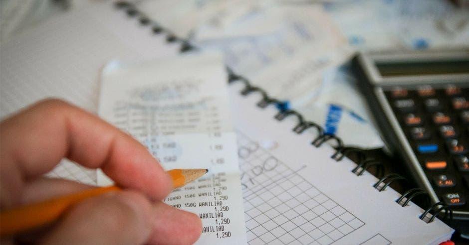 una persona cancelando sus facturas y anotando números en una libreta