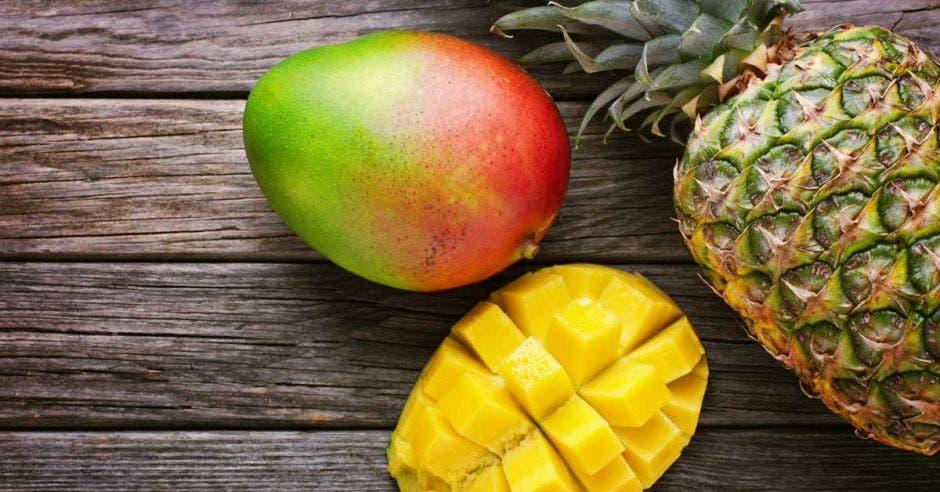 un mango y dos piñas colocadas en una mesa