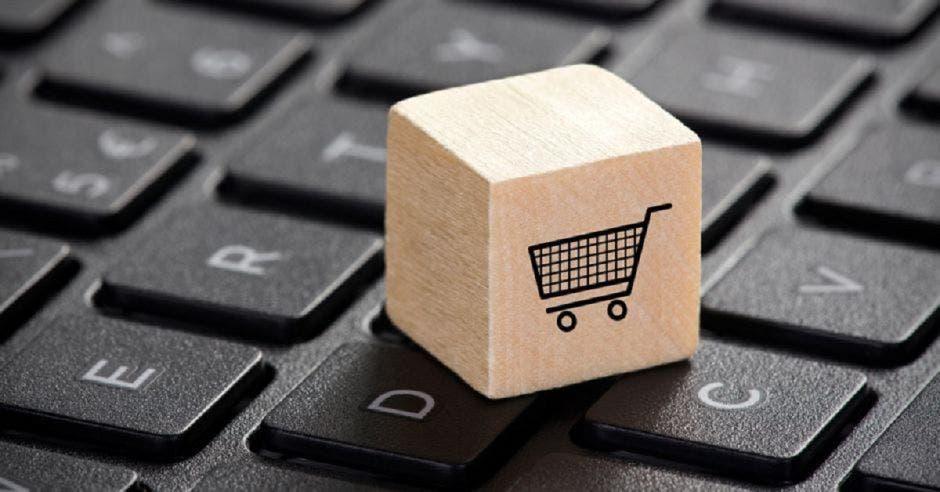 Un teclado de una computadora y un cubo con un dibujo de un carrito de compras