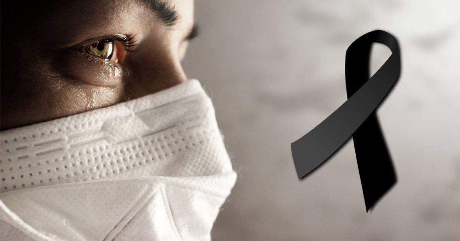 Una persona con una mascarilla y al lado un lazo negro
