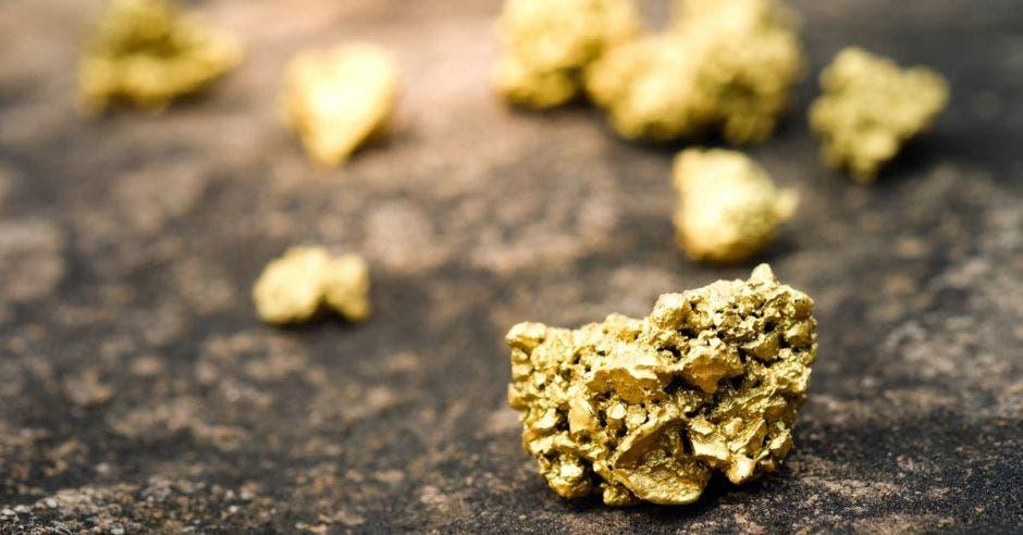 pepitas de oro colocadas sobre una mesa